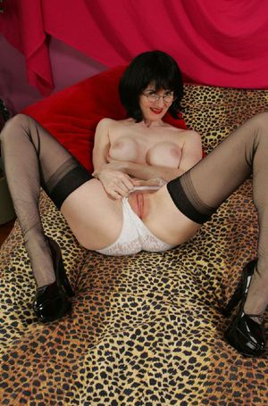 Brunette mature lady stripping and exposing her big tits and pussy