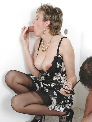 Mature femdom in stockings sucking and jerking a prick through a gloryhole