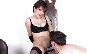Hot mature femdom torturing a blindfolded man with a big dildo