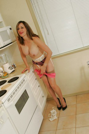 Mature fetish babe with big tits stripping off her clothes in the kitchen