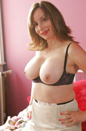 Busty mature babe showcasing her big tits and rubbing her slit