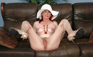 Stunning granny in glasses stripping and spreading her legs