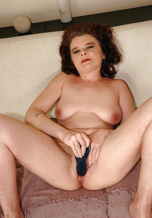 Lusty granny with big tits pushes a huge dildo in her cunt