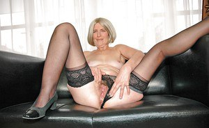 Blonde granny in stockings shows off her hairy pussy under lingerie
