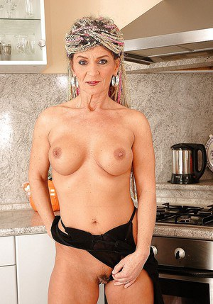 Fuckable granny with big jugs stripping off her lingerie in the kitchen