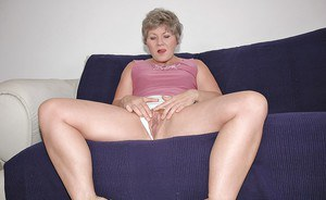 Mature lady sucking on a big dildo and pushing it in her wet cunt