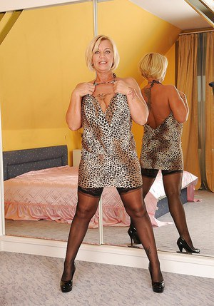 Lusty mature blonde slipping off her dress and posing in stockings