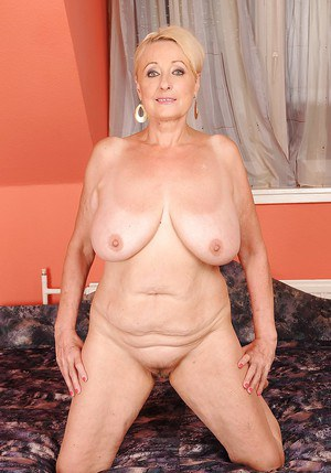 Fatty mature blonde with big jugs stripping and posing naked on the bed