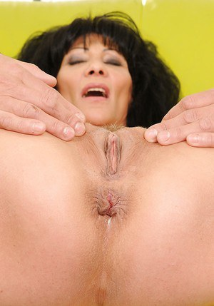 Stunning mature brunette stripping and exposing her trimmed pussy