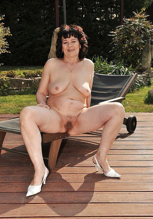 Chubby mature brunette Helena May slipping off her bikini outdoor
