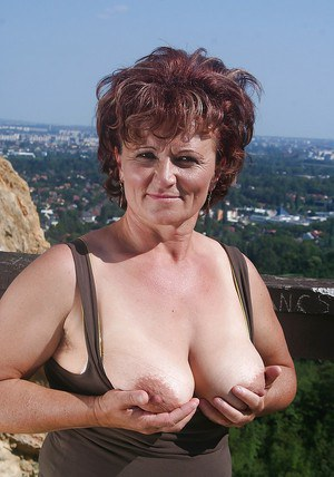 Naughty granny uncovering her fatty body with flabby boobs outdoor