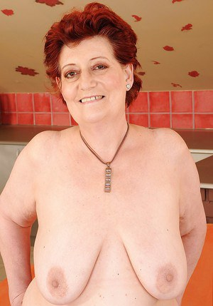 Fatty redhead granny with big flabby tits taking off her lingerie