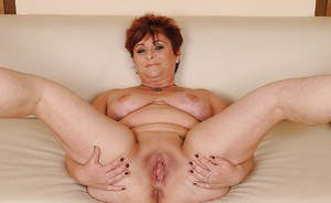 Buxom granny slipping off her lingerie and spreading her legs