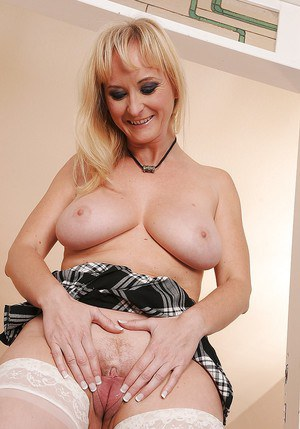 Busty mature blonde with no panties under her skirt exposing her pussy
