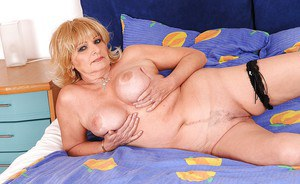 Curvaceous granny taking off her lingerie and spreading her legs
