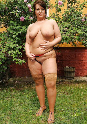 Seductive mature plumper in stockings taking off her dress outdoor
