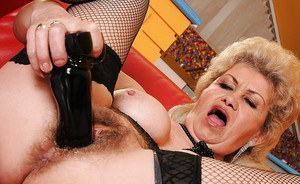 Slutty granny in stockings strips to push a huge dildo in her pussy