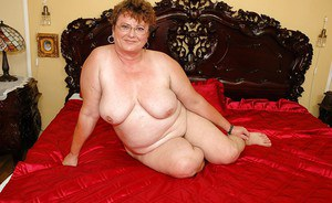 Fatty granny in glasses bends to spread her ass and expose her cunt