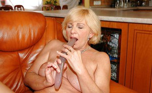 Granny with big tits sucking on a big dildo to push it in her cunt