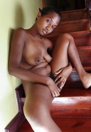 Busty ebony babe taking off her clothes and exposing her shaggy twat