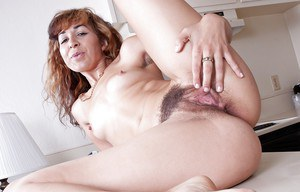 Lusty babe with hairy pussy Kitty McMuffin stripping in the kitchen