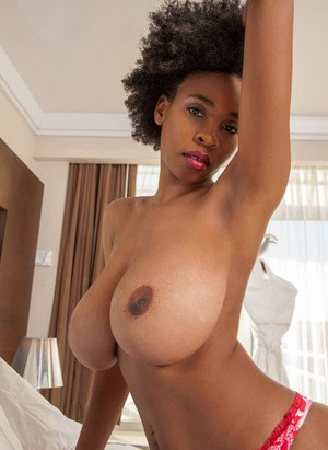 Ravishing ebony babe in glasses uncovering her massive boobs