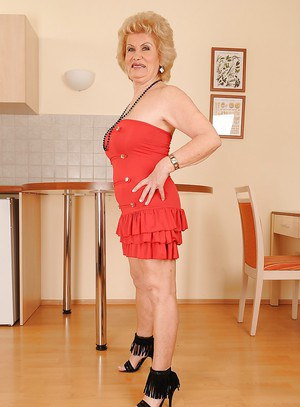 Big busted granny on high heels stripping off her dress and posing naked
