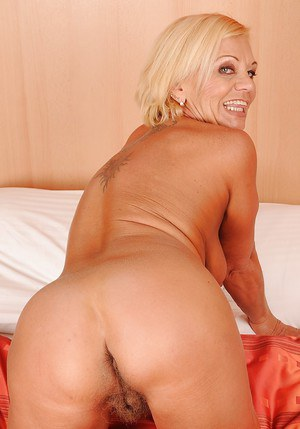 Big busted blonde granny stripping off her lingerie on the bed