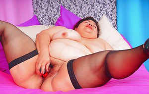 Fatty mature brunette taking off her lingerie and toying her bush