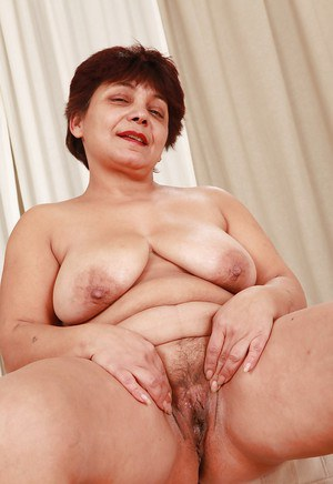 Fatty mature brunette with big tits stripping and showcasing her bush