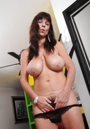 Busty mature babe Sage Hughes stripping and exposing her unshaven cunt