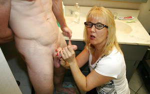 Lastful mature blonde in glasses sucking and jerking off a dick in the bath