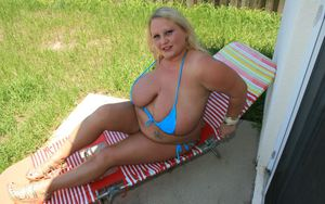 Blonde plumper in tiny bikini uncovering her massive flabby boobs outdoor