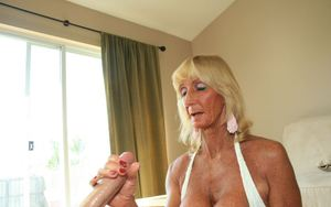 Big busted blonde granny gives a titjob and strokes a young cock