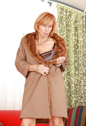 Blond mature seductress denudes from lingerie and poses topless