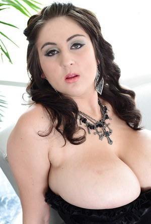 Curvy brunette posing in stockings with huge boobs popping out of her girdle