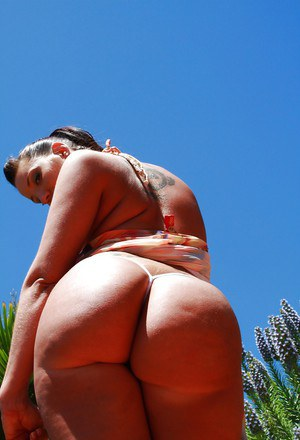 Naughty chick Kelly Divine uncovering her big jugs and fatty butt outdoor