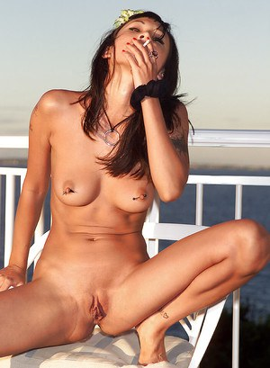 Sexy brunette with shaved pussy and pierced nipples pissing outdoor