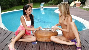 Sweet amateur lesbians playing with a huge strapon by the pool