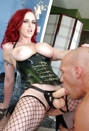 Busty femdom in fishnet stockings is into strapon action with submissive guy