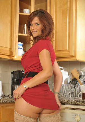 Busty mature lady in stockings Syren De Mer stripping in the kitchen