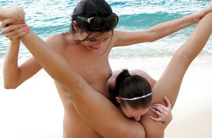 Seductive teenage lesbians stripping and caressing each other on the beach
