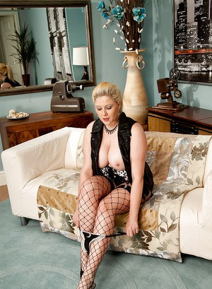 Curvaceous mature blonde in fishnet stockings stripping and spreading her legs