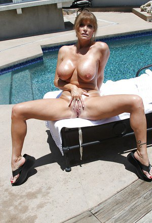Graceful mature lady with big jugs slipping off her bikini by the pool