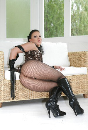 Seductive fetish MILF with long sexy legs posing in BDSM outfit