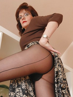 Seductive mature lady in black nylon pantyhose doing upskirt