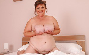 Big busted mature plumper posing barely clothed on the bed