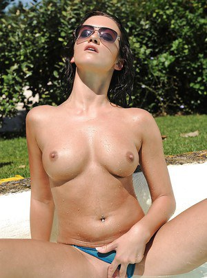 Seductive brunette in sunglasses uncovering her tempting body by the pool