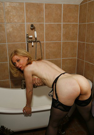 Naked mature blonde in stockings Nina Hartley posing in the bath