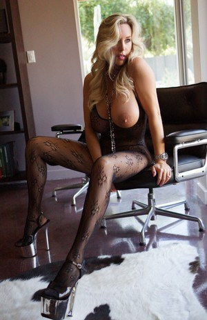 Full-bosomed blonde babe on high heels posing in pantyhose suit